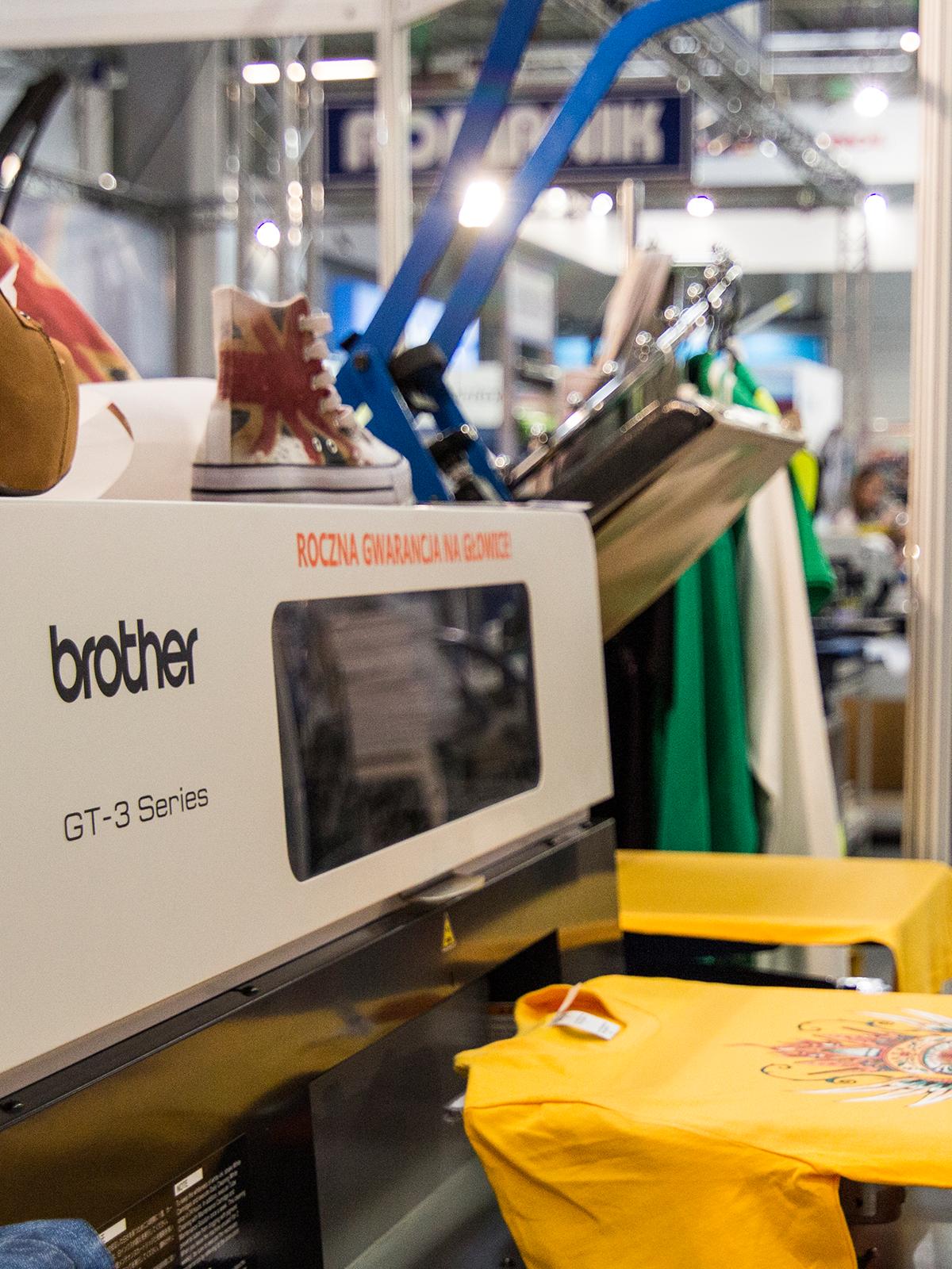 Biała maszyna marki bother naprowadzająca kolorowe nadruki na koszulkach koloru żółtego