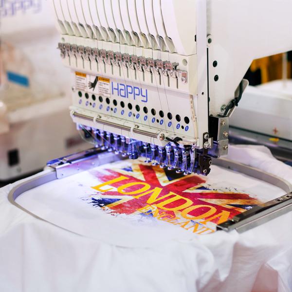 Biała, nowoczesna maszyna marki Happy generująca haft komputerowy