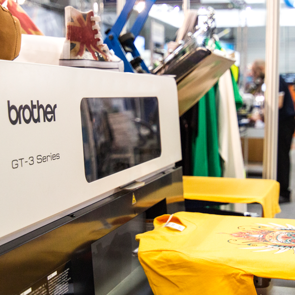 Biała maszyna marki bother produkująca nadruki na koszulkach